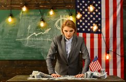 Bild av den allvarliga kvinnan med pengar som står över USA flaggan royaltyfri bild