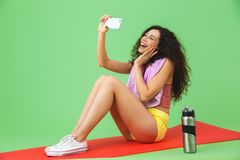 Bild av den caucasian flicka20-tal i sportswear med handduken över halsen som tar selfiefotoet, medan sitta på kondition som är m arkivfoto