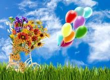 Bild av den dekorativa små mannen, blommor och baloons på en cykel mot himlen Royaltyfri Fotografi