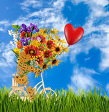 Bild av den dekorativa små mannen, blommor och baloons på en cykel mot himlen Arkivbild