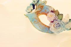Bild av den delikata blåa eleganta venetian maskeringen över trävit bakgrund Selektivt fokusera Arkivbild