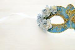 Bild av den delikata blåa eleganta venetian maskeringen över trävit bakgrund Selektivt fokusera Arkivfoto