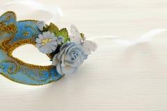 Bild av den delikata blåa eleganta venetian maskeringen över trävit bakgrund Selektivt fokusera Arkivbilder