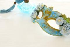 Bild av den delikata blåa eleganta venetian maskeringen över trävit bakgrund Selektivt fokusera Royaltyfri Bild