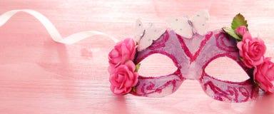 Bild av den delikata eleganta venetian maskeringen över trärosa bakgrund Selektivt fokusera Royaltyfri Foto