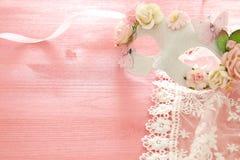 Bild av den delikata eleganta venetian maskeringen över trärosa bakgrund Selektivt fokusera Fotografering för Bildbyråer