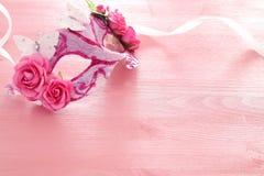 Bild av den delikata eleganta venetian maskeringen över trärosa bakgrund Selektivt fokusera Arkivfoto