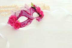 Bild av den delikata eleganta venetian maskeringen över trävit bakgrund Selektivt fokusera Fotografering för Bildbyråer