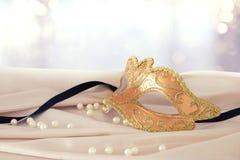 Bild av den eleganta guld- venetian maskeringen över delikat bakgrund för siden- tyg Royaltyfri Bild
