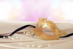 Bild av den eleganta guld- venetian maskeringen över delikat bakgrund för siden- tyg Arkivbild