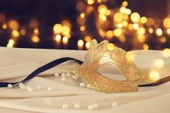 Bild av den eleganta guld- venetian maskeringen över delikat bakgrund för siden- tyg Royaltyfri Foto