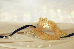 Bild av den eleganta guld- venetian maskeringen över delikat bakgrund för siden- tyg Royaltyfri Fotografi