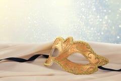 Bild av den eleganta guld- venetian maskeringen över delikat bakgrund för siden- tyg Arkivbilder
