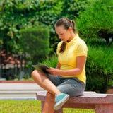 Bild av den eleganta unga flickan som använder en minnestavlaPC som sitter på vara Royaltyfri Fotografi