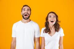 Bild av den glade den folkmannen och kvinnan i grundläggande kläder som ler, medan stå tillsammans isolerat över gul bakgrund arkivfoto