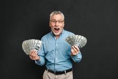 Bild av den glade vuxna man60-tal med hållande pengar två f för grått hår Royaltyfri Bild