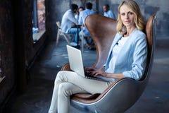 Bild av den gladlynta kontorskvinnan med blont hår i affärskläder som sitter på stol och arbetar med bärbar datorkontoret royaltyfri foto