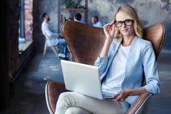 Bild av den gladlynta kontorskvinnan med blont hår i affärskläder som sitter på stol och arbetar med bärbar datorkontoret fotografering för bildbyråer