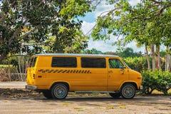 Bild av den gula klassiska taxiskåpbilen mellan gröna träd Arkivfoton