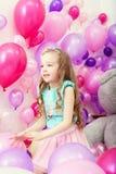 Bild av den gulliga lilla flickan som spelar bland ballonger royaltyfri foto