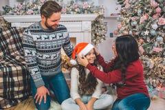Bild av den härliga familjen i dekorerat julrum Den unga kvinnan sätter den röda hatten på flickans huvud De ler till varje arkivbilder
