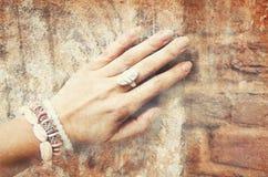 Bild av den härliga kvinnliga handen med person som tillhör en etnisk minoritetprydnader på en bakgrund av den forntida stenvägge arkivfoton