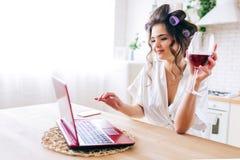 Bild av den hållande ögonen på filmen för härlig hushållerska på bärbar dator- och drinkvin i kök Arbete hemma Oförsiktig hemmafr fotografering för bildbyråer