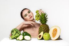 Bild av den h?rliga unga brunettkvinnan med frukter och gr?nsaker p? tabellen som rymmer gr?na druvor i hand isolerade royaltyfria foton