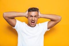 Bild av den ilskna grabb30-tal i det vita t-skjorta skrika och gripande huvudet arkivfoton