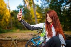 Bild av den lyckliga flickan som fotograferar sig i höstskog Arkivfoto