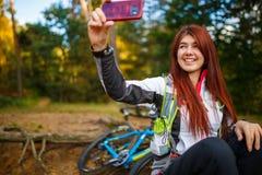 Bild av den lyckliga flickan som fotograferar sig i höstskog Royaltyfria Bilder