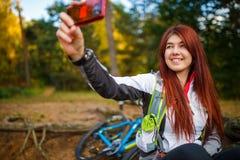 Bild av den lyckliga flickan som fotograferar sig i höstskog Royaltyfri Foto