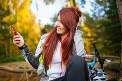Bild av den lyckliga kvinnan med mobiltelefonen i höstskog Fotografering för Bildbyråer