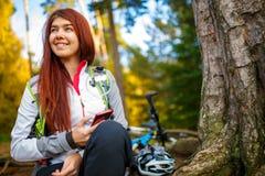 Bild av den lyckliga kvinnan med mobiltelefonen i höstskog Arkivfoton