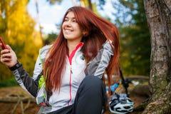 Bild av den lyckliga kvinnan med smartphonen i höstskog Fotografering för Bildbyråer