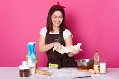 Bild av den lyckliga kvinnan som hemma knådar deg i kök och att förbereda sig för påskferie som bakar varma arga bullar, gla royaltyfri bild