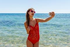 Bild av den lyckliga le kvinnan som använder telefonkameran och gör selfie Royaltyfri Bild