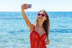 Bild av den lyckliga le kvinnan som använder telefonkameran och gör selfie Royaltyfri Fotografi
