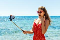 Bild av den lyckliga le kvinnan som använder telefonkameran och gör selfie Arkivfoton