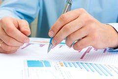 Bild av den manliga handen som pekar på affärsdokumentet under diskussion på mötet Arkivfoto