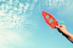 Bild av den manliga handen som rymmer en raket mot himlen fantasi och framgångbegrepp arkivfoto