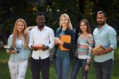 Bild av den multietniska gruppen av kandidatstudenter som utomhus står royaltyfria bilder