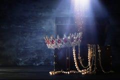 Bild av den mystiska öppnade gamla träskattbröstkorgen med ljus och drottningen/konungkronan med röda rubinstenar medeltida peri  Royaltyfri Foto