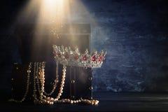 Bild av den mystiska öppnade gamla träskattbröstkorgen med ljus och drottningen/konungkronan med röda rubinstenar medeltida peri  Arkivfoto