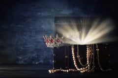 Bild av den mystiska öppnade gamla träskattbröstkorgen med ljus och drottningen/konungkronan med röda rubinstenar medeltida peri  Arkivbilder