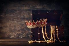 Bild av den mystiska öppnade gamla träskattbröstkorgen med ljus och drottningen/konungkronan med röda rubinstenar medeltida peri  Arkivbild