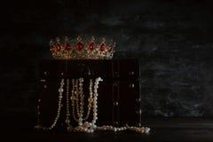 Bild av den mystiska öppnade gamla träskattbröstkorgen med ljus och drottningen/konungkronan med röda rubinstenar medeltida peri  Fotografering för Bildbyråer