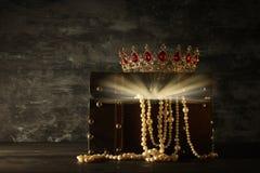 Bild av den mystiska öppnade gamla träskattbröstkorgen med ljus och drottningen/konungkronan med röda rubinstenar medeltida peri  Royaltyfri Bild