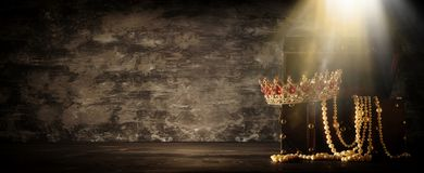 Bild av den mystiska öppnade gamla träskattbröstkorgen med ljus och drottningen/konungkronan med röda rubinstenar medeltida peri  Arkivfoton