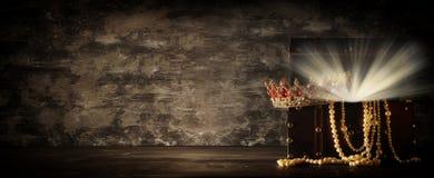 Bild av den mystiska öppnade gamla träskattbröstkorgen med ljus och drottningen/konungkronan med röda rubinstenar medeltida peri  Royaltyfria Foton